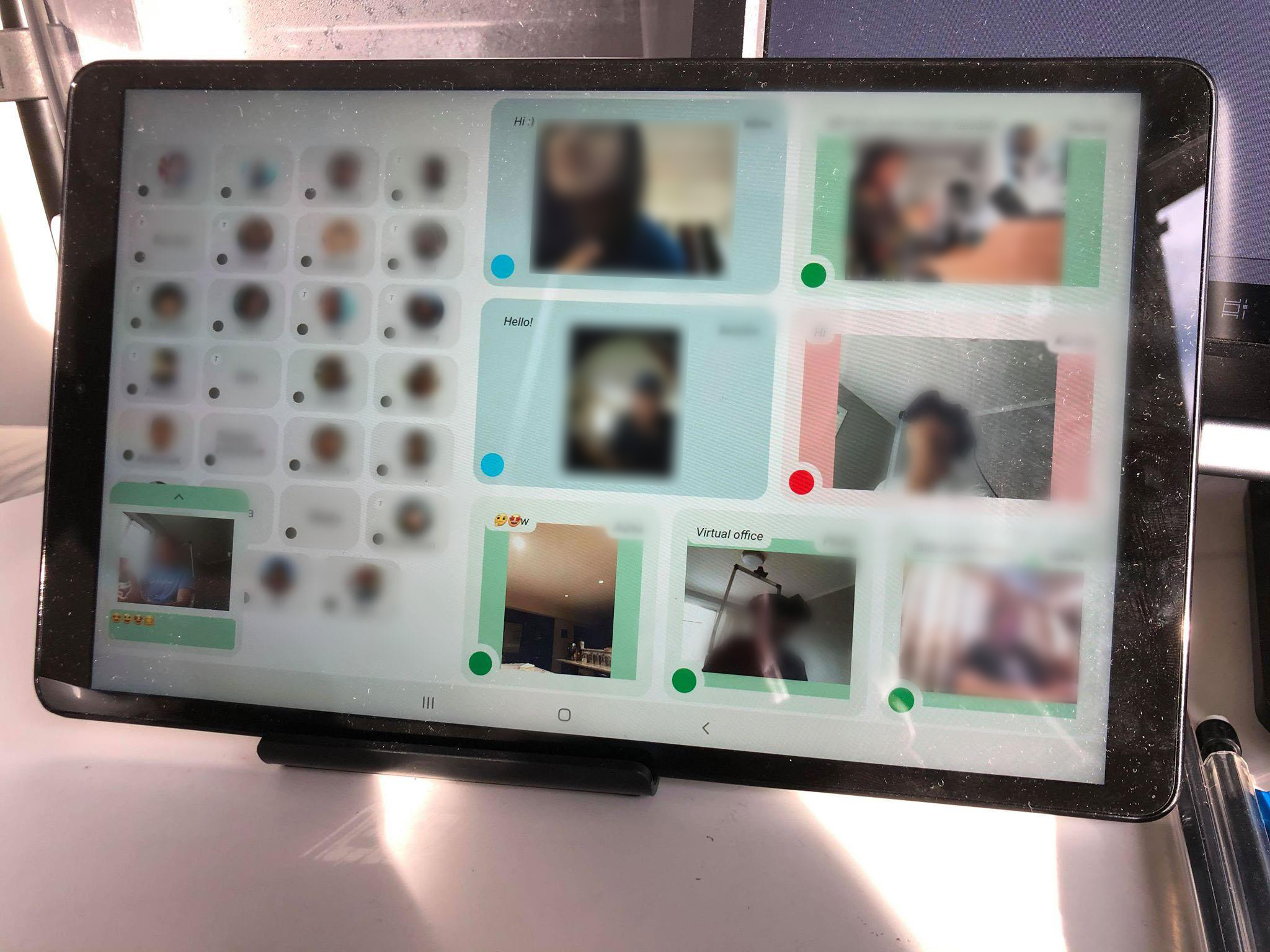 Photo of the tablet in use. Seven video feeds are displayed. Each is of a friend who is on camera and can also see you through the camera on the tablet. Each video has a colored border representing the status of the user. In the photo, four users are green, two are blue and one is red. There are also a number of gray regions with profile pictures depicting users who are offline. The photo is heavily blurred to protect the privacy of the users in the photo.